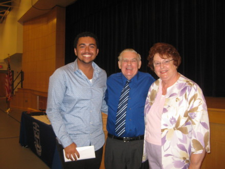 Henry Hudson senior Jordan Holoday receives an Eric P. Donoghue music scholarship from Peter and Louise Donoghue during the school's awards assembly.