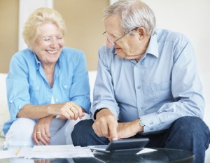 Senior couple happy over the results after calculating their expenses